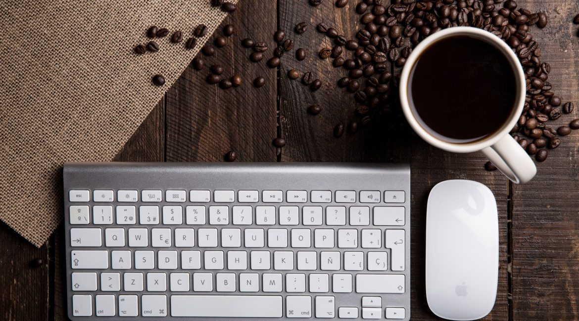 flat lay photography of apple magic keyboard mouse and mug filled with coffee beside beans